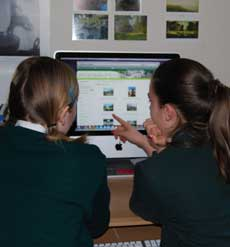 Two children looking at parks images on a computer screen