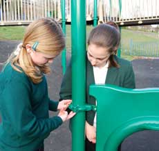 Two children examining the fixings on park play equipment