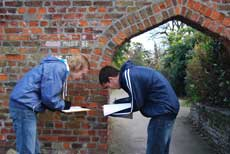Students examining the brickwork of a gateway
