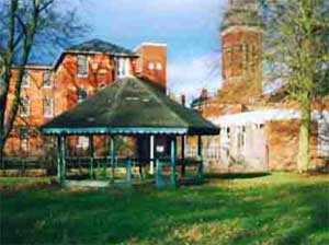 The colour photograph shows the bandstand against the brick buildings of the Northampton County Lunatic Asylum when it was St Crispin's Hospital in 2002.